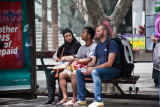 Three on seat at bus stop