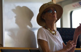 Lady on ferry in hat with reflection