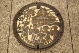 Manhole cover depicting traditional festivities