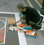 A Street Artist copying the work of Mucha