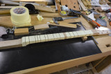 Fretboard glued on, frets banged in, all bandaged up for fret-end dressing