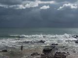 A lone fisherman under stormy skies