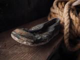 Petit soulier trouvé dans la terre battue de la cave