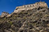 Volcanic plug cliff face of Castle Rock with red Valerian and Great Hall of the Royal Palace of Edinburgh Castle with blue sky i
