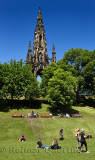 People and tourists in Princes Street Gardens park under the Scott Monument in Edinburgh Scotland UK with blue sky
