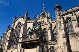 Bronze sculpture of Charles II on horseback at south side of St Giles' Cathedral with crown steeple Edinburgh Scotland United Ki