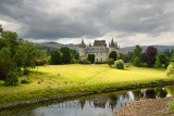Inveraray Castle reflected in the River Aray with dark clouds and golden grass in the Scottish Highlands Scotland UK