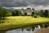 Inveraray Castle reflected in the River Aray at Loch Fyne with dark clouds and golden grass in the Scottish Highlands Scotland U
