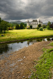 Inveraray Castle in sun reflected in the River Aray at Loch Fyne with dark clouds and sunshine in the Scottish Highlands Scotlan
