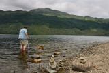 Convalescing man walking with crutch and dog on leash in Loch Lommond freshwater lake at Ben Lamond mountain Scotland UK