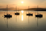 Setting sun over Ardmucknish Bay at North Connel and Oban Airport with sailboats in silhouette