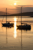 Full sun reflecting on the water of Ardmucknish Bay at North Connel and Oban Airport with sailboats in silhouette