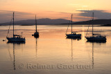 Red sky at sunset over Ardmucknish Bay at North Connel and Oban Airport with sailboats in silhouette
