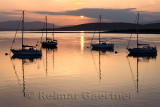 Red sky at sunset reflecting on the water of Ardmucknish Bay at North Connel and Oban Airport with sailboats in silhouette