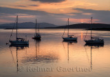 Red sky and clouds at sunset reflecting on the water of Ardmucknish Bay at North Connel with sailboats and Lismore island in sil