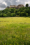 Stirling Castle high on Castle Hill with clouds and yellow field of buttercups in Stirling Scotland UK