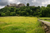 Stirling Castle high on Castle Hill with clouds and yellow buttercups in sheep pasture with stone wall in Stirling Scotland UK