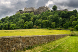 Stirling Castle on the cliff at Castle Hill in Stirling Scotland with stone wall of sheep pasture with dark clouds