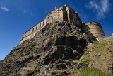 Volcanic plug cliff face of Castle Rock and Great Hall of the Royal Palace and half moon battery of Edinburgh Castle in Edinburg