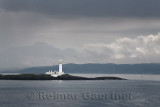 Lismore Lighthouse on Eilean Musdile Islet off Lismore Island with rain and clouds over the west coast highlands Scotland UK