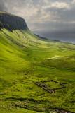 Sun breaking through clouds at Balmeanach cliffs of Creag a Ghaill green slopes and barn ruins on Loch Na Keal Isle of Mull Scot