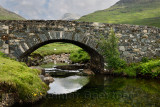 Stone bridge over the Scarsdale river with sheep and peak of Ben More mountain in distance on Isle of Mull Inner Hebrides Highla