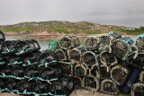 Lobster traps piled up on pier of Fionnphort fishing village at ferry terminal for Iona on Isle of Mull Scotland UK