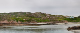 Panorama of shoreline of isolated Fionnphort fishing village on Isle of Mull Scotland with red granite rock and cracked erratic