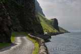 Van passing steep cliffs and rock wall of narrow Highway B8035 on the shore of Loch Na Keal on the Isle of Mull Scotland UK