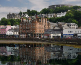 Historic buildings and McCaig's Tower on Battery Hill overlooking Oban harbour with water reflections in Oban Bay Scotland UK