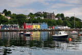 Colorful houses reflected in the water of Tobermory harbour on the Isle of Mull with moored boats Scottish Inner Hebrides Scotla