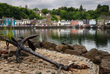 Rusted anchor on jetty and colorful houses reflected in the water of Tobermory harbour on the Isle of Mull Scottish Inner Hebrid