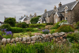Flower gardens under cloudy sky with stone houses of Baile Mor village on Isle of Iona Scotland UK