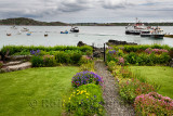 Baile Mor garden on Isle of Iona looking out to Sound of Iona and Fionnphort with docked Ferry and tour boats and sailboats Scot