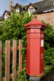 Red Royal Mail Post Office box with evergreen Hebe bush at Baile Mor village on Isle of Iona Inner Hebrides Scotland UK