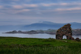Granite stone ruins of the Bishop's House next to Iona Abbey at dusk on Isle of Iona with view over Sound of Iona to Isle of Mul