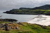 Lichen covered rocks at Sandeels Bay above sandy beach on Isle of Iona Inner Hebrides Scotland UK