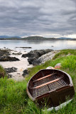 Sand beach and rocky shore of Isle of Iona with beached boat and view of Fionnphort Isle of Mull Sound of Iona Inner Hebrides Sc