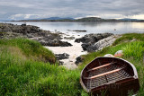Rocky shore of Isle of Iona with beached boat with Fionnphort Isle of Mull and mountains of Ben More past Sound of Iona Inner He
