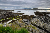 Sand beach and rocky shore under clouds on Isle of Iona with boats on Sound of Iona and Fionnphort Isle of Mull mountains Scotla