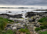 Sand beach and rocky shore and clouds on Isle of Iona with boat on Sound of Iona Inner Hebrides Scotland UK