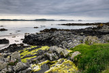 Sand beach and rocky shore with grass and algae on Isle of Iona with boat on Sound of Iona Inner Hebrides Scotland UK