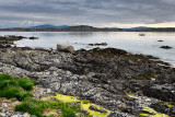 Rocky shore of Isle of Iona with sailboats on Sound of Iona and view of Fionnphort Isle of Mull mountains Inner Hebrides Scotlan