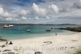 White sand beach of Martyr's Bay on Isle of Iona looking at Isle of Mull and boats in Sound of Iona Inner Hebrides Scotland UK