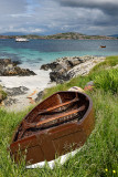 Sand beach and rocky shore of Isle of Iona with beached boat and view of Isle of Mull mountains of Ben More and tour boat on Sou