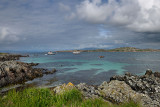 Rocky shore of Isle of Iona looking at Isle of Mull and mountains of Ben More and tour boats in Sound of Iona Inner Hebrides Sco