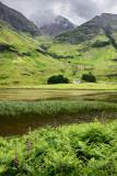 Achnambeithach cottage on Loch Achtriochtan under Aonach Dubh waterfall and Bidean nam Bian mountains Glen Coe valley Scotland U