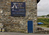Stone wall of Argyll Arms Hotel with blue sign open to non residents and beer kegs in Bunessan on Isle of Mull Scotland UK