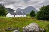 White washed stone Black Rock Cottage climbing hut in Glen Coe with Stob Dhearg of Buachaille Etive Mor mountain range Scottish