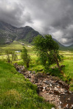 Stream to River Coupall valley with white cottage at foot of Buachaille Etive Mor mountains Glen Coe under dark clouds Scotland